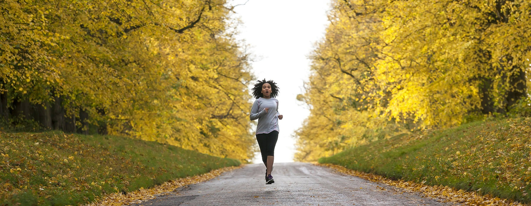 woman running on paved trial